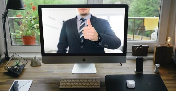 man on iMac screen giving thumbs up