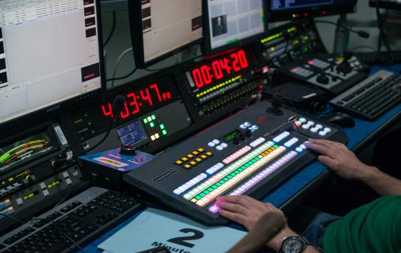 Producer using control room equipment: timer, soundboard, screens
