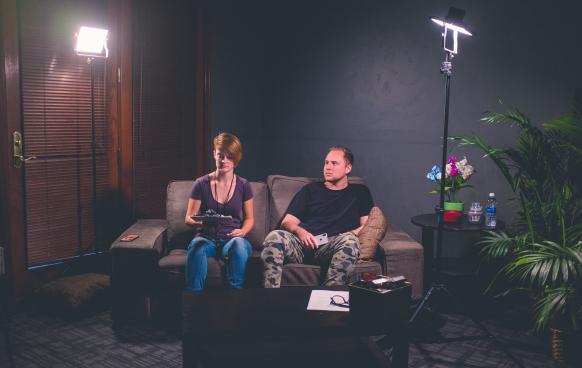 Man & Woman sitting on couch with production equipment