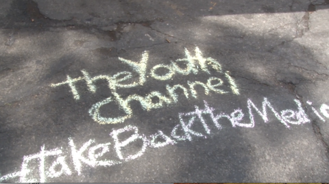 "Concrete ground with chalk letters: ""The youth Channel #TakeBackTheMedia"""