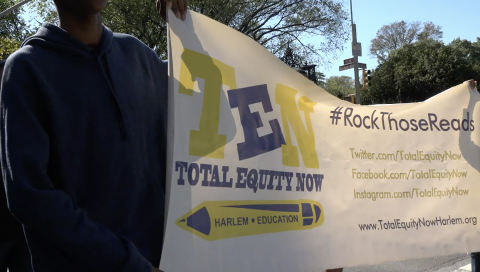 "person holding banner with ""ten total equity now"" logo"